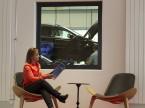 Eine Kundin wartet auf ihr Auto. Durch das grosse Fenster in die Werkstatt kann sie die Service-Arbeiten verfolgen.